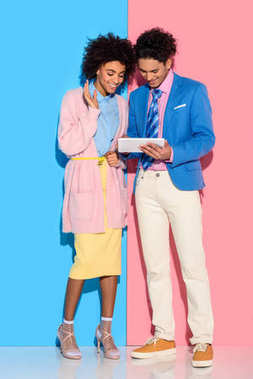 Smiling couple using digital tablet on pink and blue background