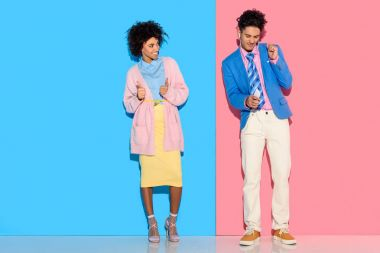 Happy couple standing in distance of each other on pink and blue background