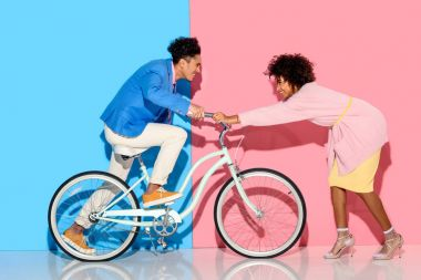 Happy couple having fun with bicycle on pink and blue background