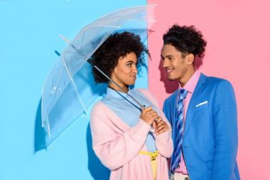 Smiling couple standing close to each other under umbrella on pink and blue background