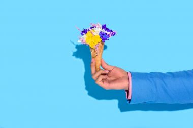 Cropped image of man hand holding flowers on blue background