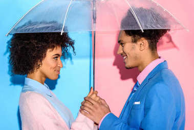 Young couple standing close to each other under umbrella on pink and blue background