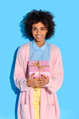 portrait of cheerful african american woman with gift in hands against blue wall