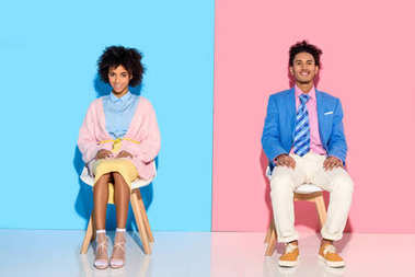 smiling african american couple sitting on chairs against pink and blue wall backdrop