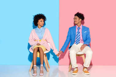 african american couple holding hands while sitting on chairs against pink and blue wall backdrop