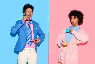 Stylish african american couple with toy teacups with pink and blue wall backdrop