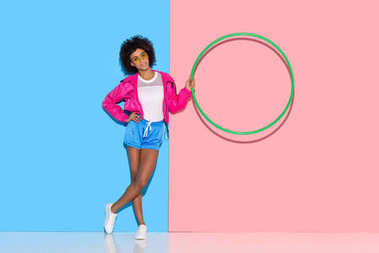 Woman in sportswear standing with hoop in hand on pink and blue background