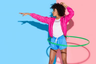 Sporty woman posing while exersizing with hoop on pink and blue background