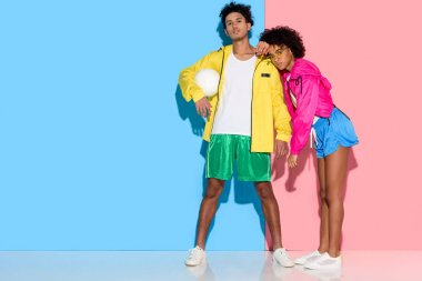 Attractive young couple in sportswear standing against  pink and blue background