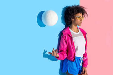 Attractive girl standing against wall and throwing up ball on pink and blue background
