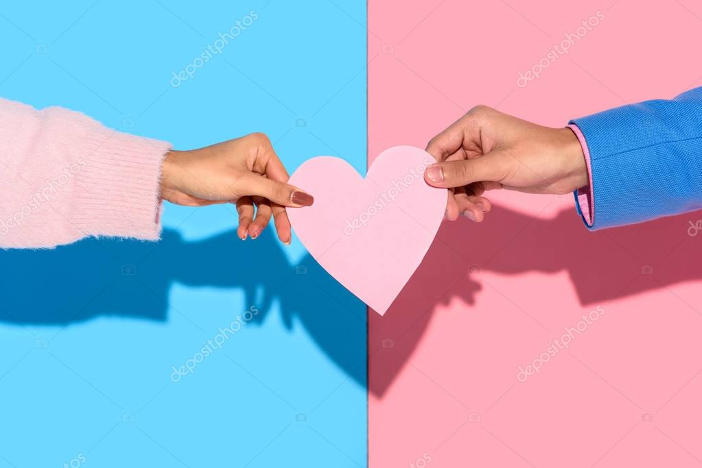 Close-up view of man giving girl heart card on pink and blue background stock vector