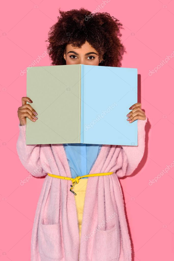 obscured view of african american woman with book in hands looking at camera with pink wall backdrop