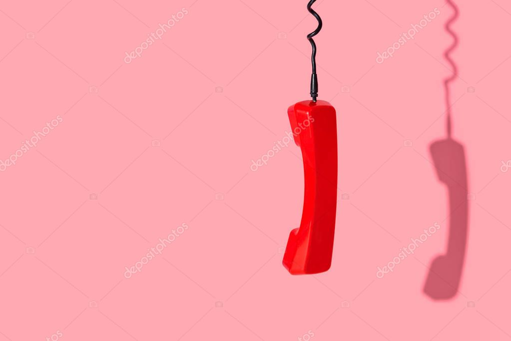 View of old telephone handset on pink background