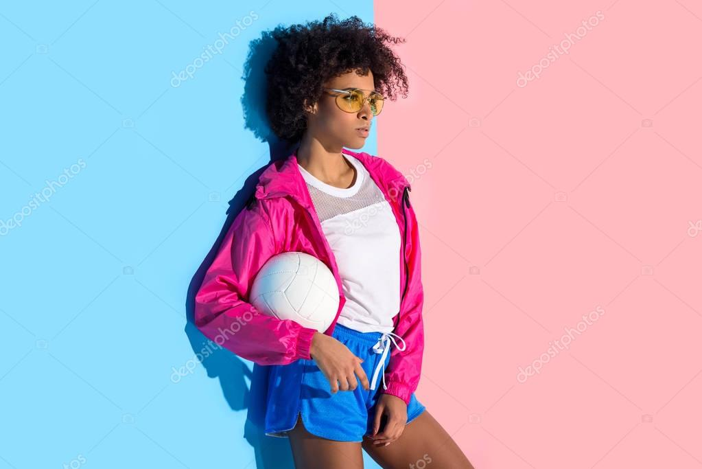 Young girl in glasses holding  ball and looking at away on pink and blue background