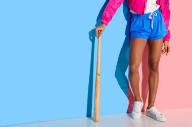 Young girl in bright clothes with baseball bat