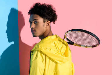 Young bright african american guy holding tennis racket on shoulder on pink and blue background