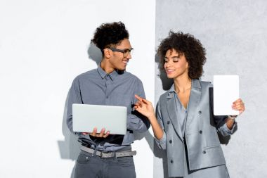 Young african amercian businessman with laptop and businesswoman with tablet in hand on grey and white background