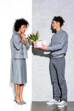 Young african amercian man gives girl a bouquet of flowers and gift on grey and white background