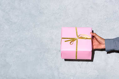 Close-up view of man giving gift box on grey background