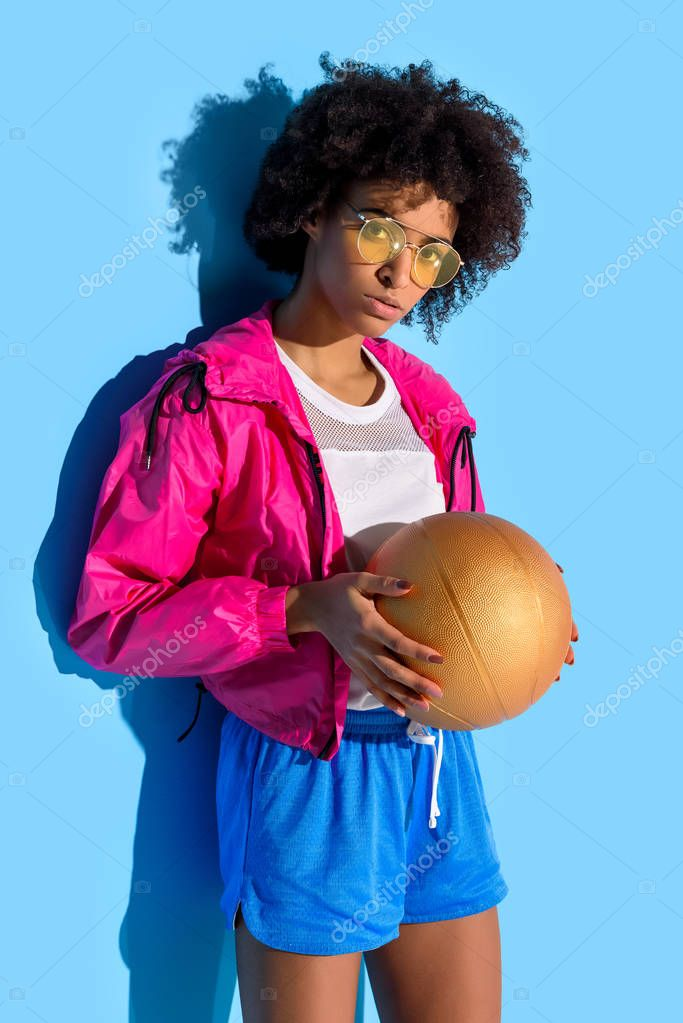 Young girl in glasses holding basketball ball and looking at camera on blue background