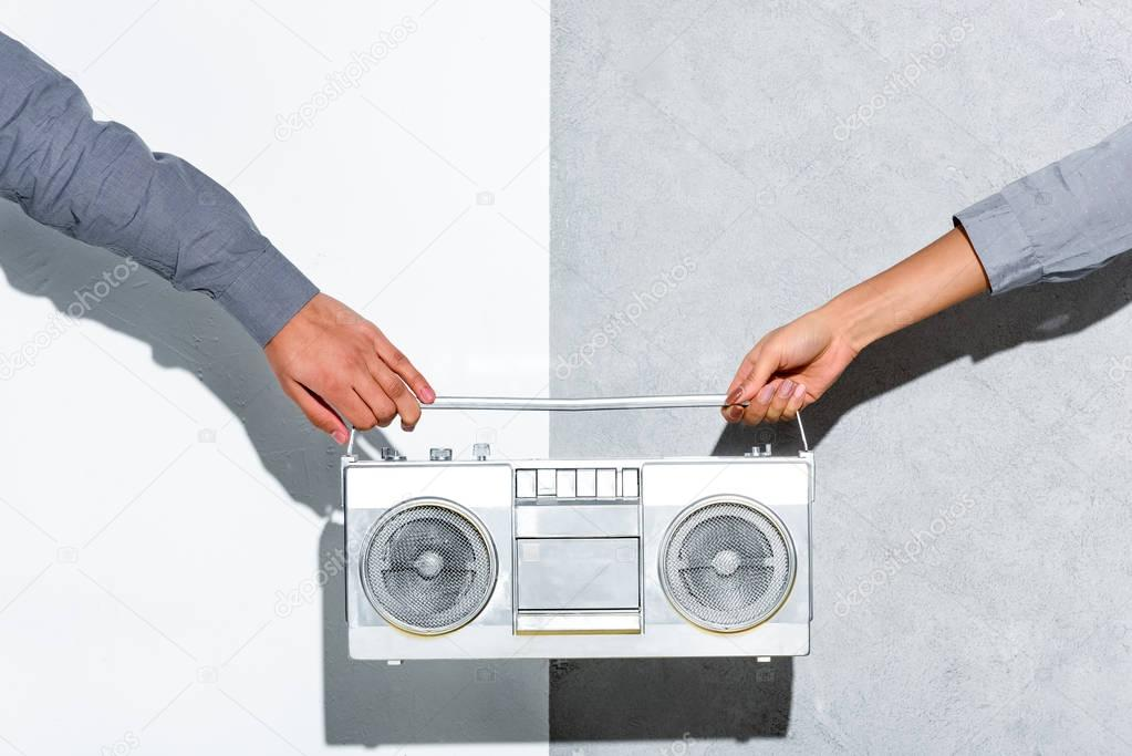 Close-up view of young couple holding boombox in hands on grey and white background