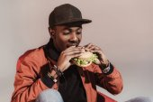 young african american man eating hamburger isolated on grey