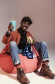 happy young african american man eating hamburger and drinking from paper cup while sitting on bean bag chair in studio