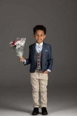smiling african american kid standing with bouquet of flowers on gray