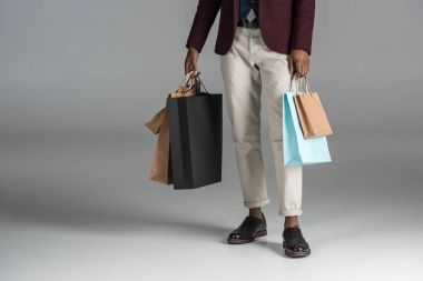 low section of man with paper shopping bags on grey background