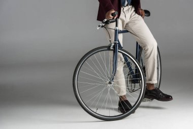 Low section of man siting on bike on grey background