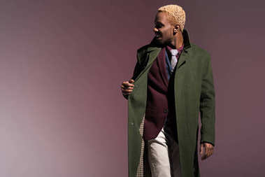 Stylish young african american man wearing green winter coat isolated on violet background