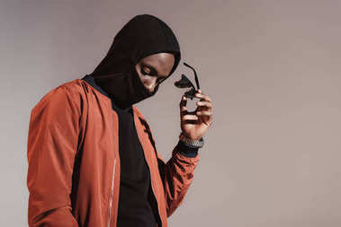 Stylish young african american man wearing hood with face mask and taking of his sunglasses isolated on light background