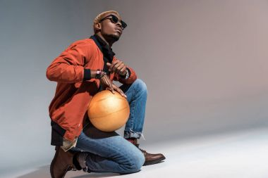 Stylish young african american man holding basketball ball on his knee