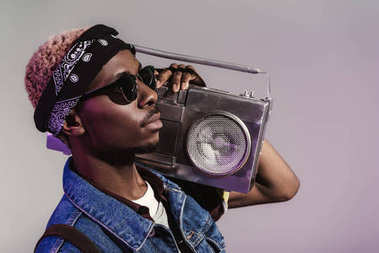 stylish young african american man in sunglasses holding tape recorder on shoulder and looking away isolated on grey