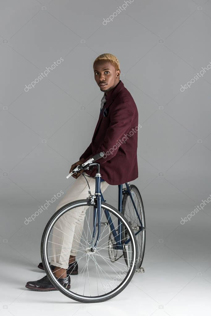 serious african man sitting on bike and looking at camera on grey background