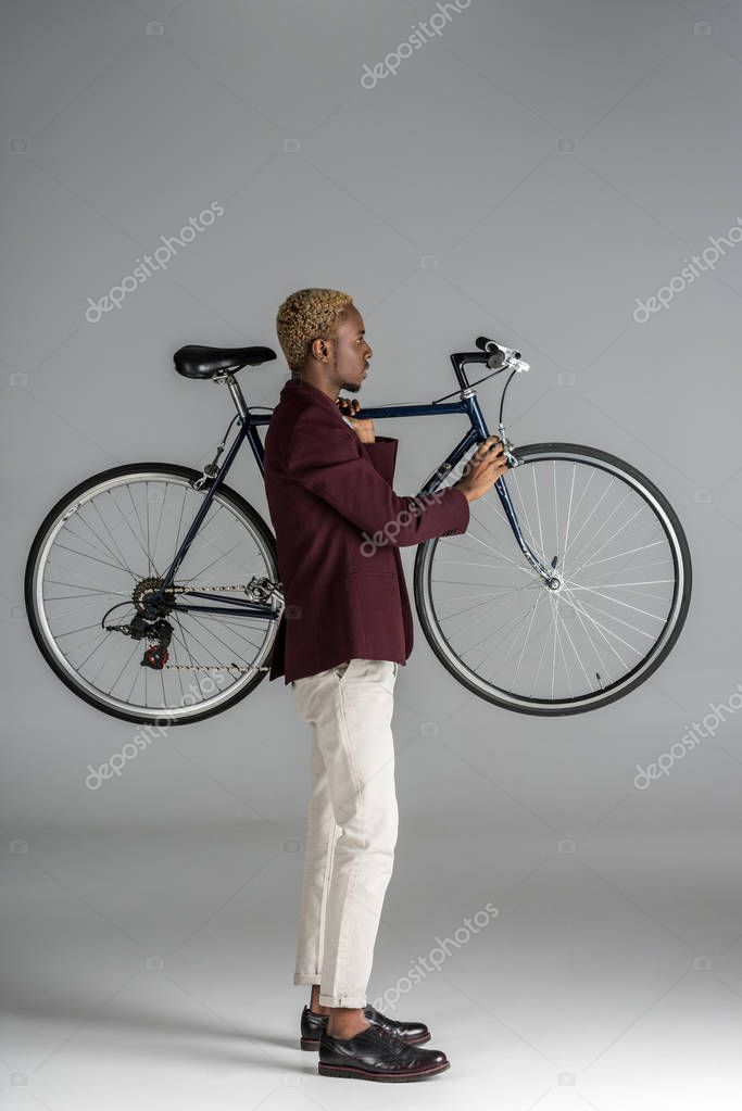 african american man holding bicycle in hands on grey background