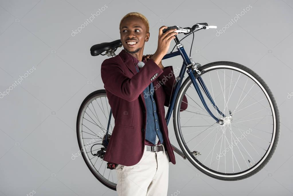 smiling african american man holding bicycle in hands isolated on grey