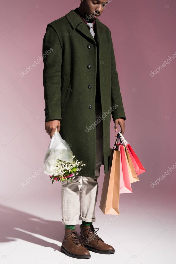 Stylish young african american man holding bouquet of flowers and bright shopping bags