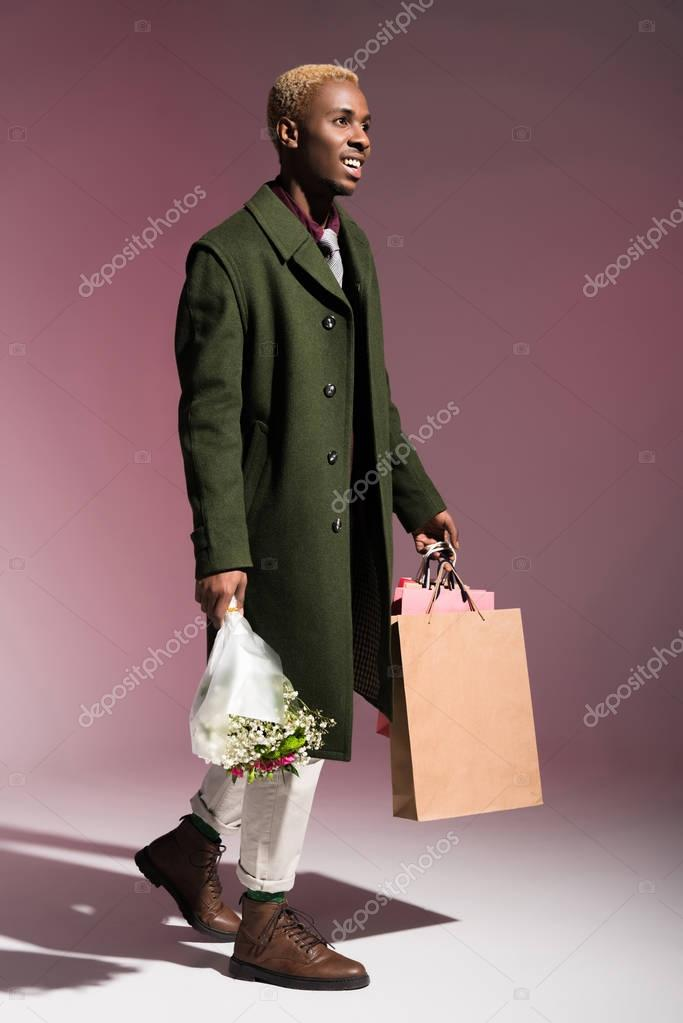 Stylish young african american man walking and carrying bouquet of flowers and shopping bags