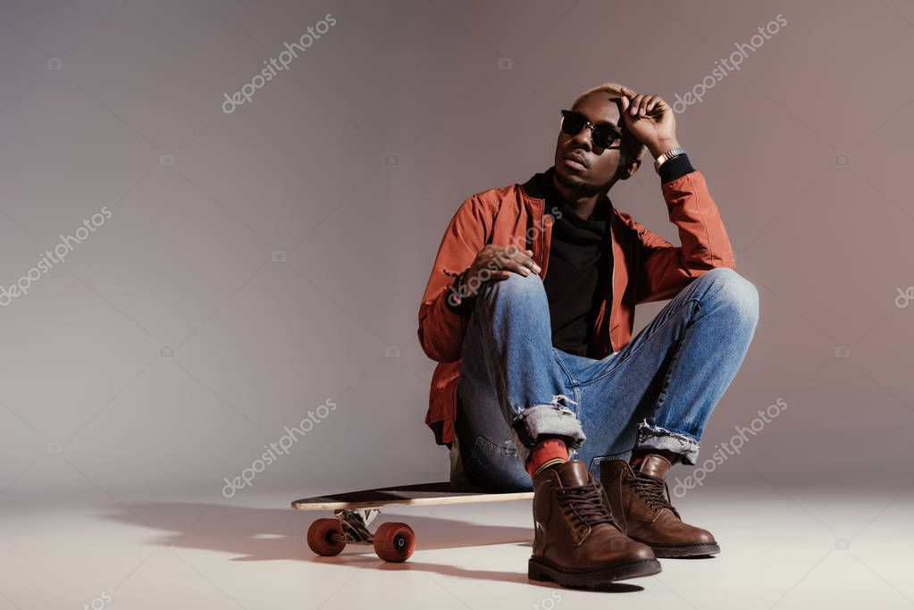 Stylish young african american skateboarder sitting on longboard