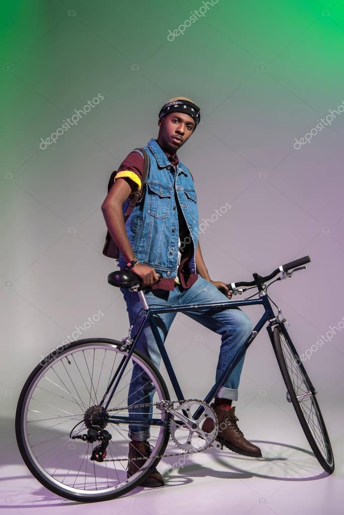 low angle view of young african american man standing with bicycle and looking at camera on grey