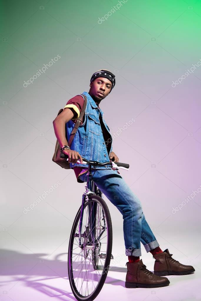 stylish young african american man sitting on bicycle and looking away on grey