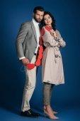 Fotografia coppia che tiene la ghirlanda di cuori rossi e che guarda lobbiettivo sullazzurro