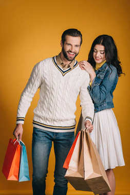 happy couple with shopping bags isolated on yellow