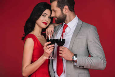 attractive couple standing with wineglasses isolated on red