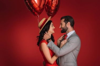 stylish couple with red balloons looking at each other isolated on red