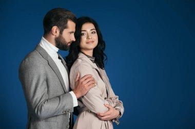 boyfriend hugging girlfriend isolated on blue