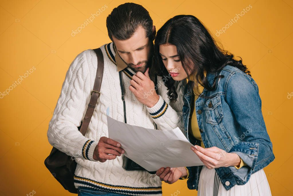 couple of tourists looking at map isolated on yellow