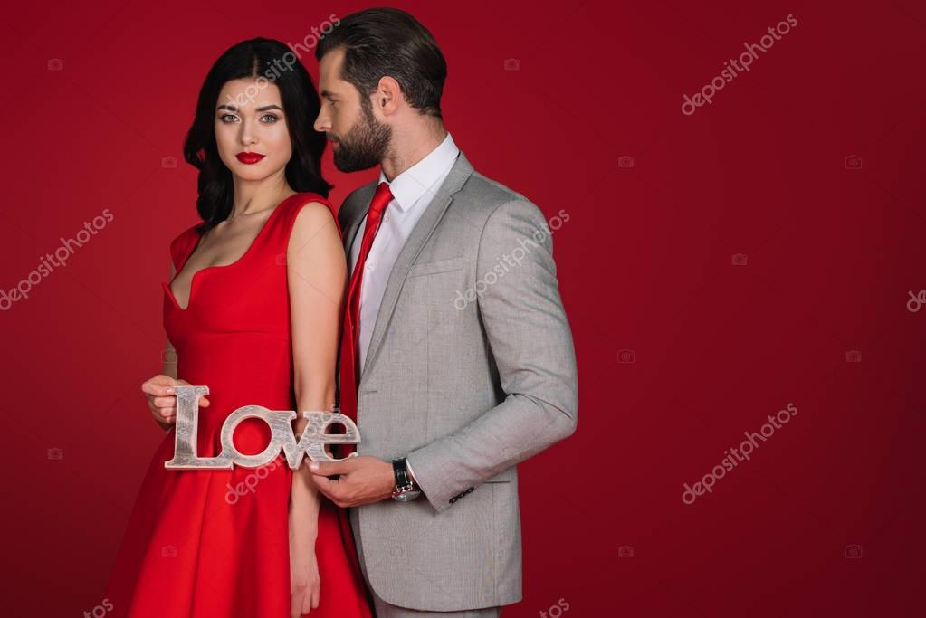 affectionate couple standing with sign love isolated on red