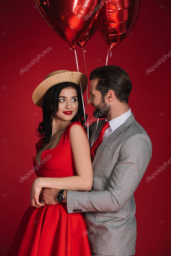 stylish couple with red balloons hugging isolated on red